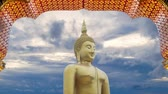 4K footage. big great powerful Buddha statue in gold color with door frame arch and beautiful time lapse of sky with cloudy at sunset or sunrise time at background. Buddha image for Buddhists