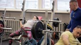 heavy : Paurlifting. The sports woman. Gym. The woman lifts heavy weight lying on a back. Training. The man does exercises. Bodybuilder lifting heavy barbell weights. The woman in the gym. The trainer insures the sports woman.