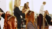 new york : The woman the hairdresser does curls for a professional hairstyle to the girl of model. The master prepares model hair before a hairstyle Stock Footage