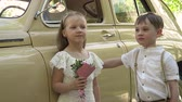 copy : The little boy with the sister poses about the big beige retro car