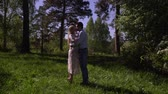 formato : Young couple kiss on a tree in a garden. The beautiful girl with the guy dernutsya by hands on a glade