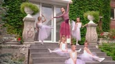 kegyelem : Little ballerinas train on a porch of ballet school with the teacher. Beautiful ballerinas carry out exercises on an extension before the ballet on a porch of school Stock mozgókép