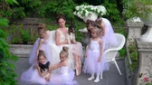 sukénka : Little ballerinas together with the teacher sit on white chairs of a recreation area