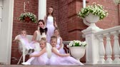 dansers : Little girls in white tutus sit on old steps of school of the ballet. Beautiful estate of ballet school. The teacher with the schoolgirls sits on a porch.. Stockvideo