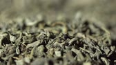 SLOW MOTION: Tea leaves fall on a pile of a green tea - Macro shot. Stok Video