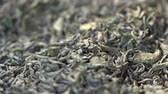 Male hand picks tea leaves for brewing. Chinese green tea. Dried tea leaves background. Macro. Beautiful dried green tea leaves closeup