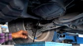 servicing : Auto Mechanic Draining Old Oil Underneath the Car Lift at the Garage