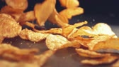 gevrek : Fresh roasted potato chips falling on black surface and rolling towards camera. Slow motion and close up shot.