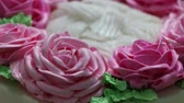 The rotation of the pink roses and green leaf of butter cream on the white cake.