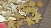 icings : Gingerbread men sprinkled with powdered sugar and lie on a brown wooden table