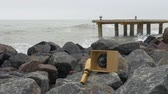 навигацион судно : Compass and telescope spyglass lying on granite rocks. Metall pier with bollards and bitts in rough sea, green yellow water and gray sky on background. Стоковые видеозаписи