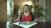 чайная ложка : Beautiful middle aged brunet woman in red dress eating food with chopsticks in fancy restaurant alone at table