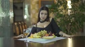 clivagem : Sexy young seductive brunet woman in black dress with cleavage eating fruits grapes alone at table in fancy restaurant Stock Footage