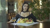 clivagem : Young seductive sexy brunet woman in black dress with cleavage eating fruits grapes alone at table in fancy restaurant Stock Footage