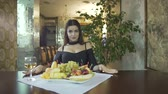 clivagem : Sexy seductive young brunet woman in black dress with cleavage eating fruits grapes alone at table in fancy restaurant Stock Footage