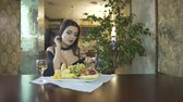 clivagem : Sexy seductive brunet young woman in black dress with cleavage eating fruits grapes alone at table in fancy restaurant