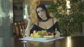 clivagem : Young seductive brunet sexy woman in black dress with cleavage eating fruits grapes alone at table in fancy restaurant