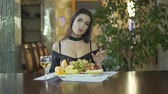 clivagem : Young sexy brunet seductive woman in black dress with cleavage eating fruits grapes alone at table in fancy restaurant Stock Footage