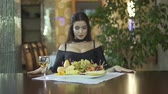 clivagem : Young brunet sexy seductive woman in black dress with cleavage eating fruits grapes alone at table in fancy restaurant