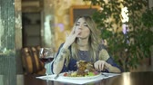golosità : Young attractive tattooed blond girl in fancy dinner restaurant licking greasy fingers inappropriate behaviour in public Filmati Stock