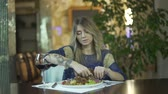 golosità : Young beautiful tattooed blond girl in fancy dinner restaurant tearing meat eating with fingers inappropriate behaviour