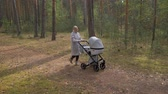 sports : Young cute mom walking in the Park with a stroller. listening to music and dancing