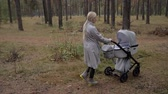 koleno : Young cute mom walking in the Park with a stroller. listening to music and dancing