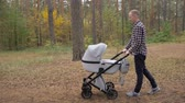 paternidade : A young father walks with a stroller in the park. A man with a newborn baby. Vídeos