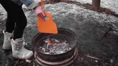 kindle : girl snowboarder to make a fire. Girl watching the fire. Slow motion
