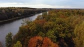 Aerial view. Flying over the river. Beautiful autumn day. The camera flies up to the river over the forest. 4k