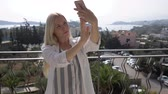 para : Young beautiful girl taking pictures of herself on the hotel terrace. The girl takes a selfie on the terrace. 4K Stock Footage