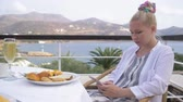 santorin : Beautiful elegant girl having breakfast at outdoor cafe with amazing view on the see. Woman use the telephone on luxury hotel terrace with sea view at resort restaurant. 4K