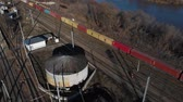fixer : Two railway workers are on the rails next to the standing freight train. Worker team assure railway service. Aerial view. 4K Stock Footage