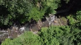 Children play and swim in a forest waterfall. Aerial view as the kids play in a mountain waterfall in the forest. 4K