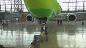 manuseio : Pushback of a passenger aircraft at the airport in hangar. The airplane nose, landing gear and towing truck close up. Stock Footage