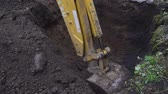 Excavator shovel digs into a ground Стоковые видеозаписи