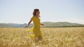 A young girl in a yellow dress with long hair running on a wheat field. Slow motion