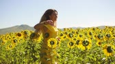 A young girl in a yellow dress runs across the field in sunflowers. Slow motion Stock Footage