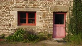 brittany : Typical french breton stone house facade with colorful window and door. Brittany, France