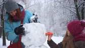 mother and her daughter playing with snowman during snow fall