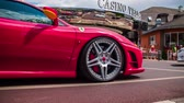 atravessar : VELDEN, AUSTRIA - JUNE 2014: Street show supercars. Very expensive cars driving through town. Red Ferrari in slow motion low angle passing by