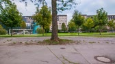 sideview : LJUBLJANA, SLOVENIA ? SEPTEMBER 2014: Driving by a green park with trees and buildings in background. Car window perspective passing a park with footpath. Stock Footage