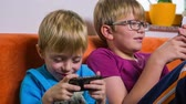 brother : Young brothers playing with smartphones. Brothers in living room enjoying on sofa playing games on smartphones. Jib shot of kids using technology toys. Stock Footage