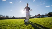 play : Boy dribble soccer ball. Running in front of person dribble and kick soccer ball with sun shining in background and blue sky.