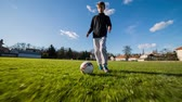 Young kid dribbling soccer ball tracking shot. Soccer player dribble camera on green field. Wideo