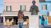 coat : Tourist taking picture of statue. Brown long haired woman with smartphone taking picture of Baldassare Galuppi statue  on Burano square on a sunny day. Shot from the back. Stock Footage