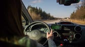 cabine : Person behind the steering wheel. Woman with long hair driving car on highway on a sunny day. Small navigation device help beside the steering wheel showing route. Stock Footage