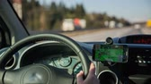 cabine : Driving with navigation map. Close up on steering wheel in car with navigation GPS device beside showing route to goal. Driving on highway on a sunny day. Stock Footage