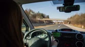 cabine : Person in car setting navigation while driving. Driving car on highway and touching the navigation device on dashboard next to steering wheel. Woman driving on a sunny day.