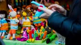 trabalho manual : Person showing bird toy at booth. Close up of toys at small booth outside, vendor demonstrating blue bird plush. Stock Footage